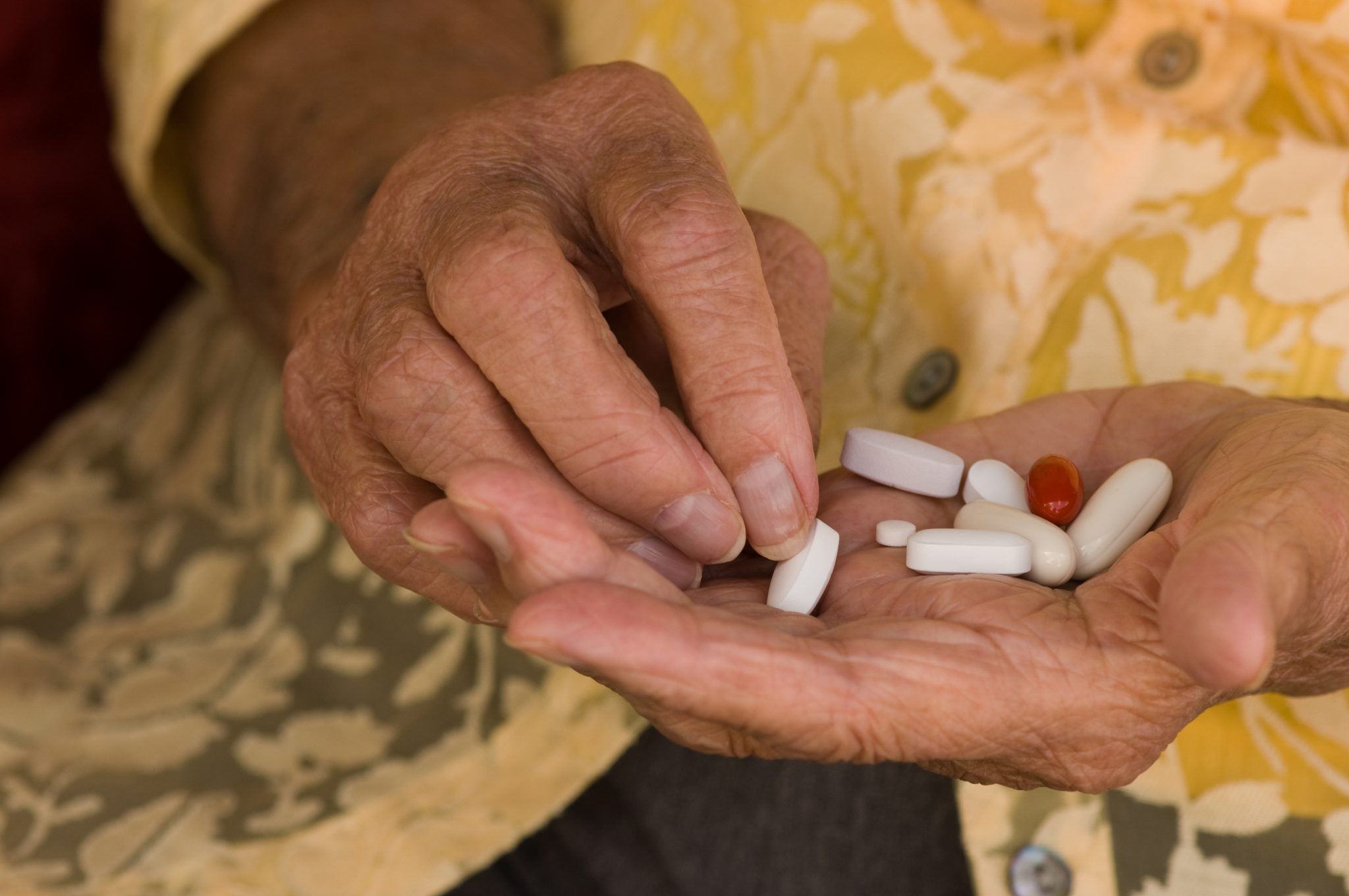 Older person's hand holding medication