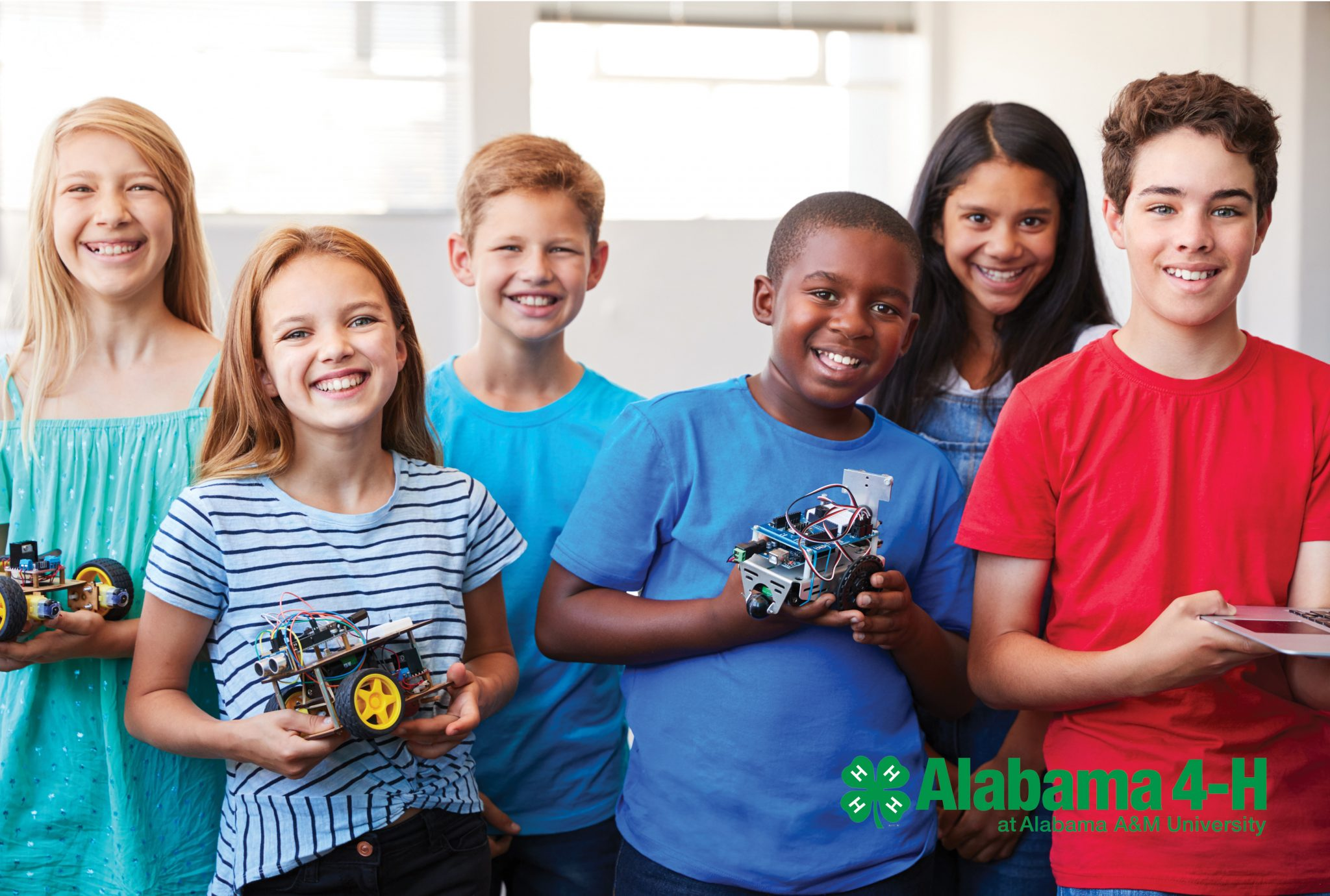 Six diverse middle school students hold up robotics projects while smiling