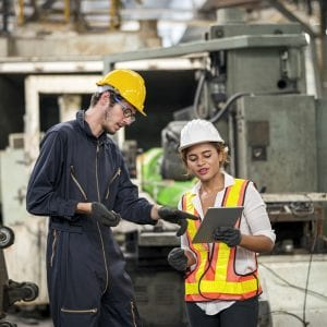 Female Maintenance Engineer and Male Maintenance technical discuss maintenance report in digital tablet.
