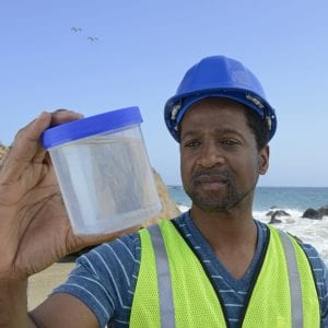 A man examines a water sample from the ocean.