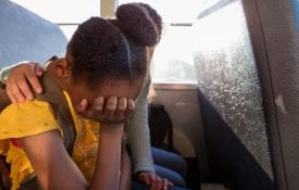 A young girl crying on a bus