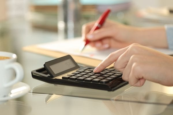 Woman hands using calculator and writing on a desk