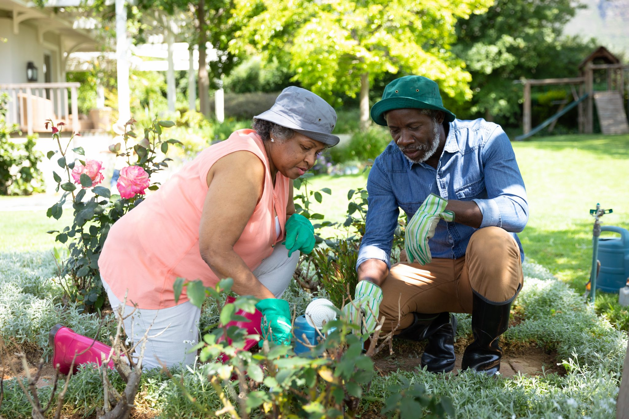 Older black couple working in the flower bed