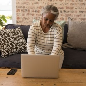 Front view of an active African American senior woman using laptop and sitting on a sofa in living room at home