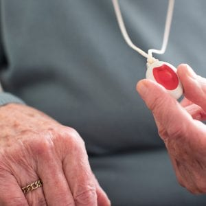 Close Up Of Unwell Senior Woman Holding Personal Alarm Button At Home