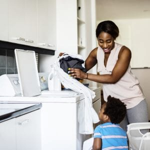 Black kid helping mom doing the laundry