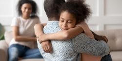 Managing family conflicts;Young african american man holding, embracing, comforting smiling happy calm black cute kid daughter, blurred mother sitting on couch on background, loving supporting family concept.