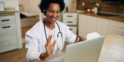 Happy African American female doctor using laptop and greeting someone while having video call in the office.