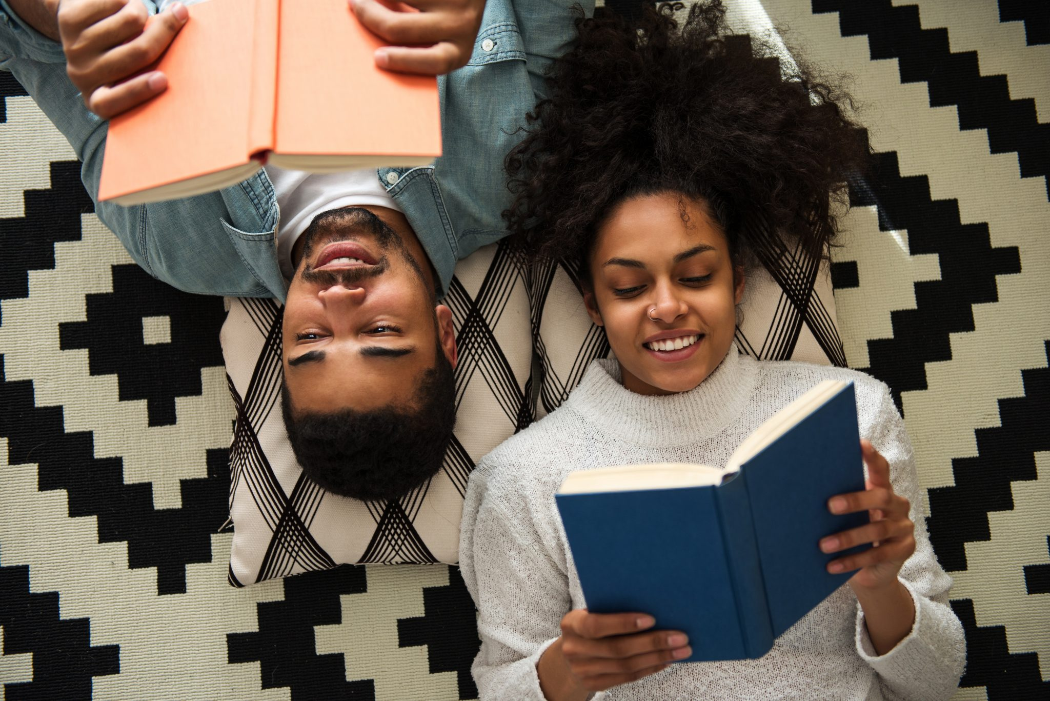 African American couple lying on the floor and reading books.