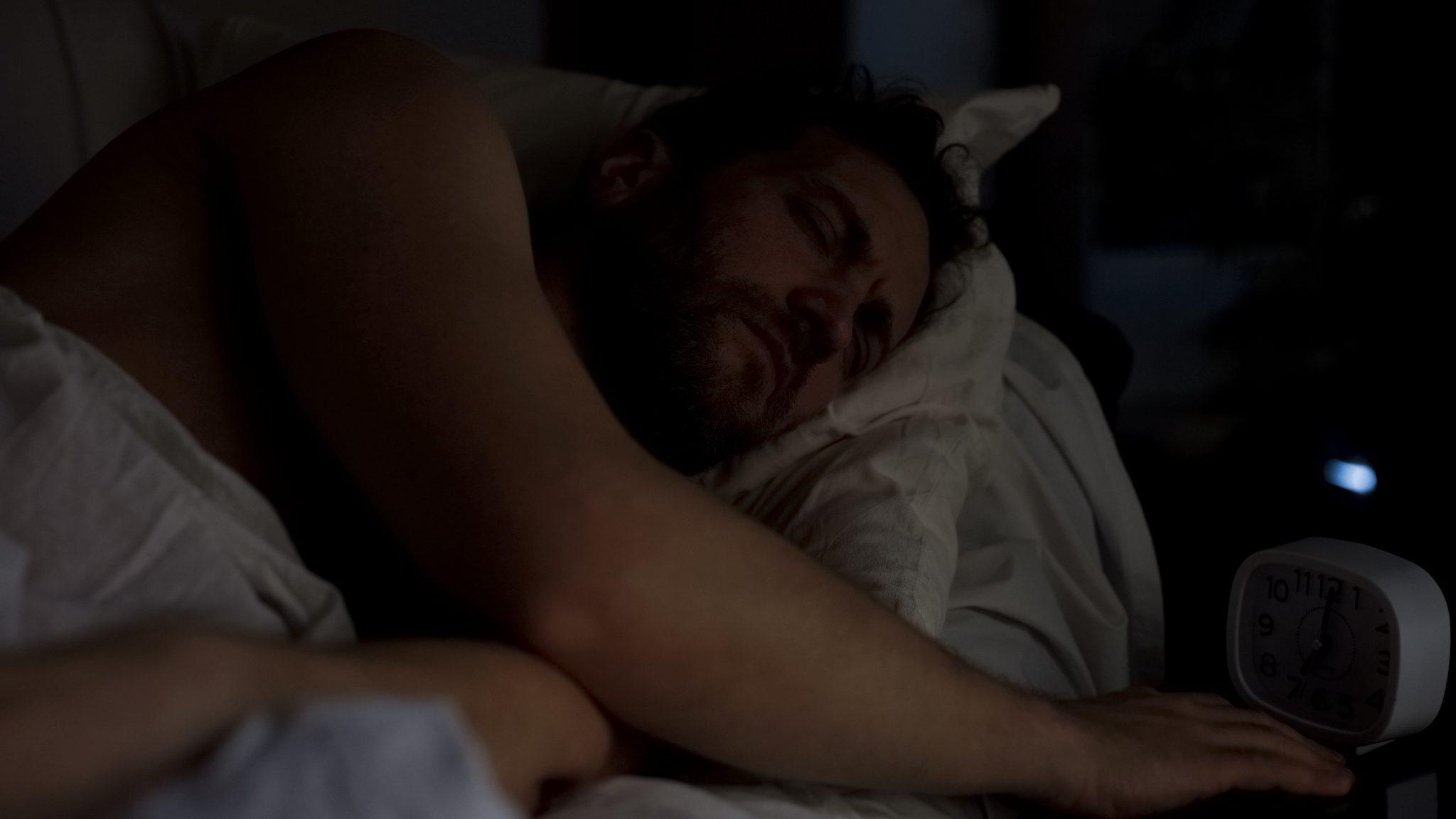 Sleeping man in a dark room
