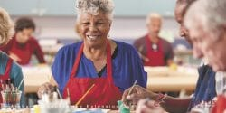 An African American older adult woman sits at a table with painting supplies wearing an apron