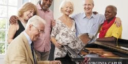 A group of elderly people gathered around a piano