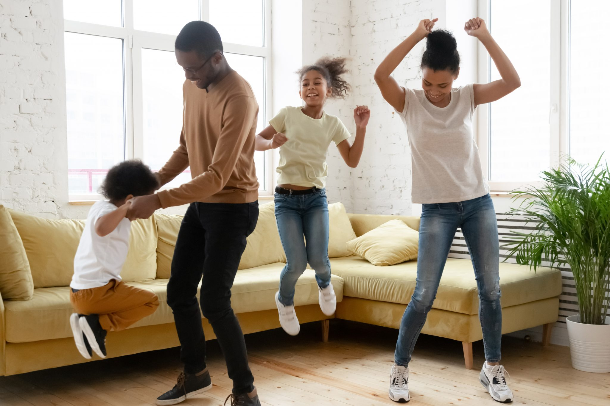 Overjoyed african American young family have fun enjoy leisure weekend at home together, happy biracial parents with small preschooler kids dance jump entertain in living room, stress free concept