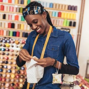 Portrait of happy african dressmaker woman in studio. Background of colorful sewing thread.