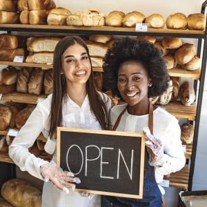 Stop by for homemade delicious bread! Loving young women embracing holding a sign together on the opening day of their small business - couple owners of the bakery smiling to the camera