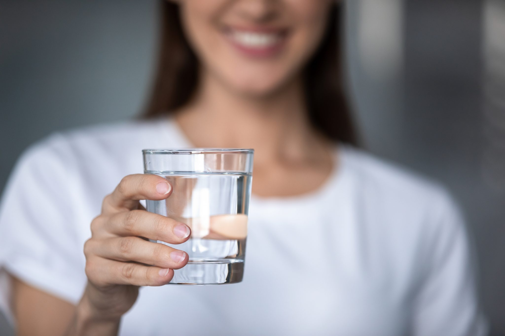 Smiling young lady holding a glass of water