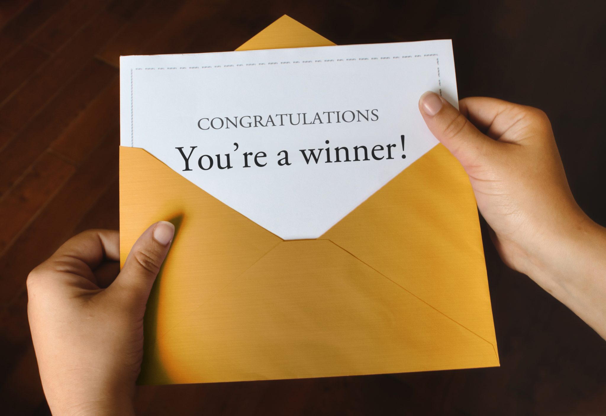 "An envelope with a card that says, ""congratulations! You're a winner"