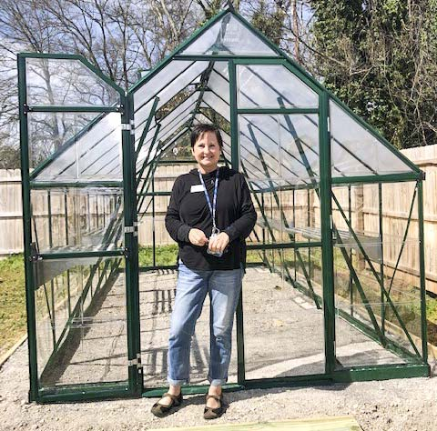 person in front of greenhouse