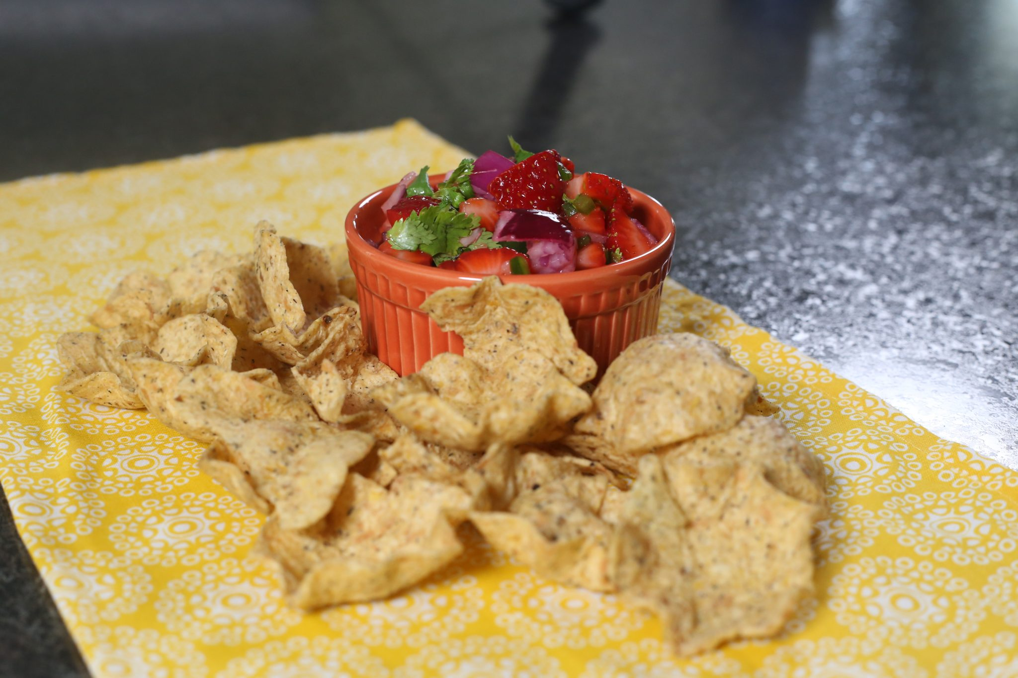 salsa, chips, brown cutting board