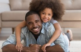 An African American Father with his daughter playing happily on the living room floor.