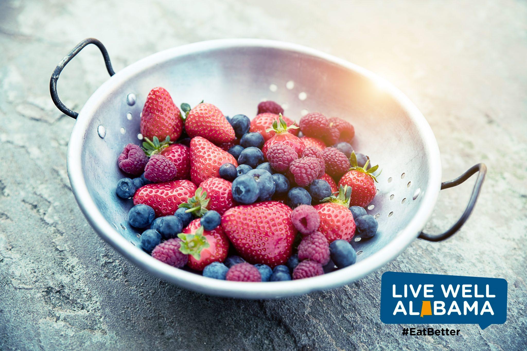 Strawberries, blueberries and raspberries in colander