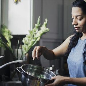 Woman washing food in colander