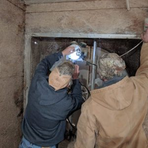 Figure 1. A broiler producer replacing a 1 horsepower (hp) electric motor on a tunnel ventilation fan