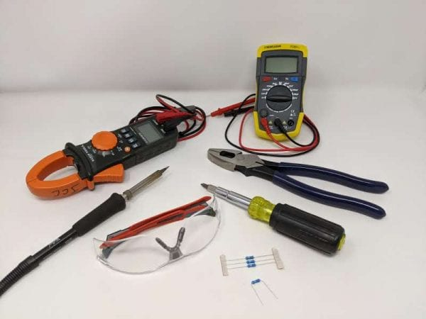 Figure 1. Tools to perform a motor capacitor test: electrical multimeter, capacitance meter (optional), insulated pliers, multi-tool driver, electrical resistors, and soldering iron. Always wear safety glasses.