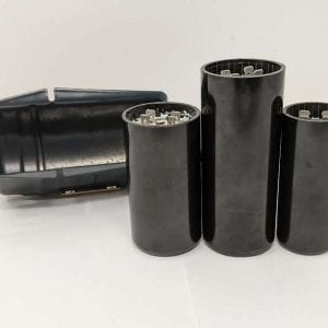 Figure 12. Three start capacitors with different lengths and diameters. The center capacitor has the correct physical dimensions to fit snuggly in the metal housing on the left.
