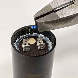 Figure 6a. Electrically insulated pliers are used to hold a 20k Ohm resistor across the capacitor tabs to drain any stored energy.