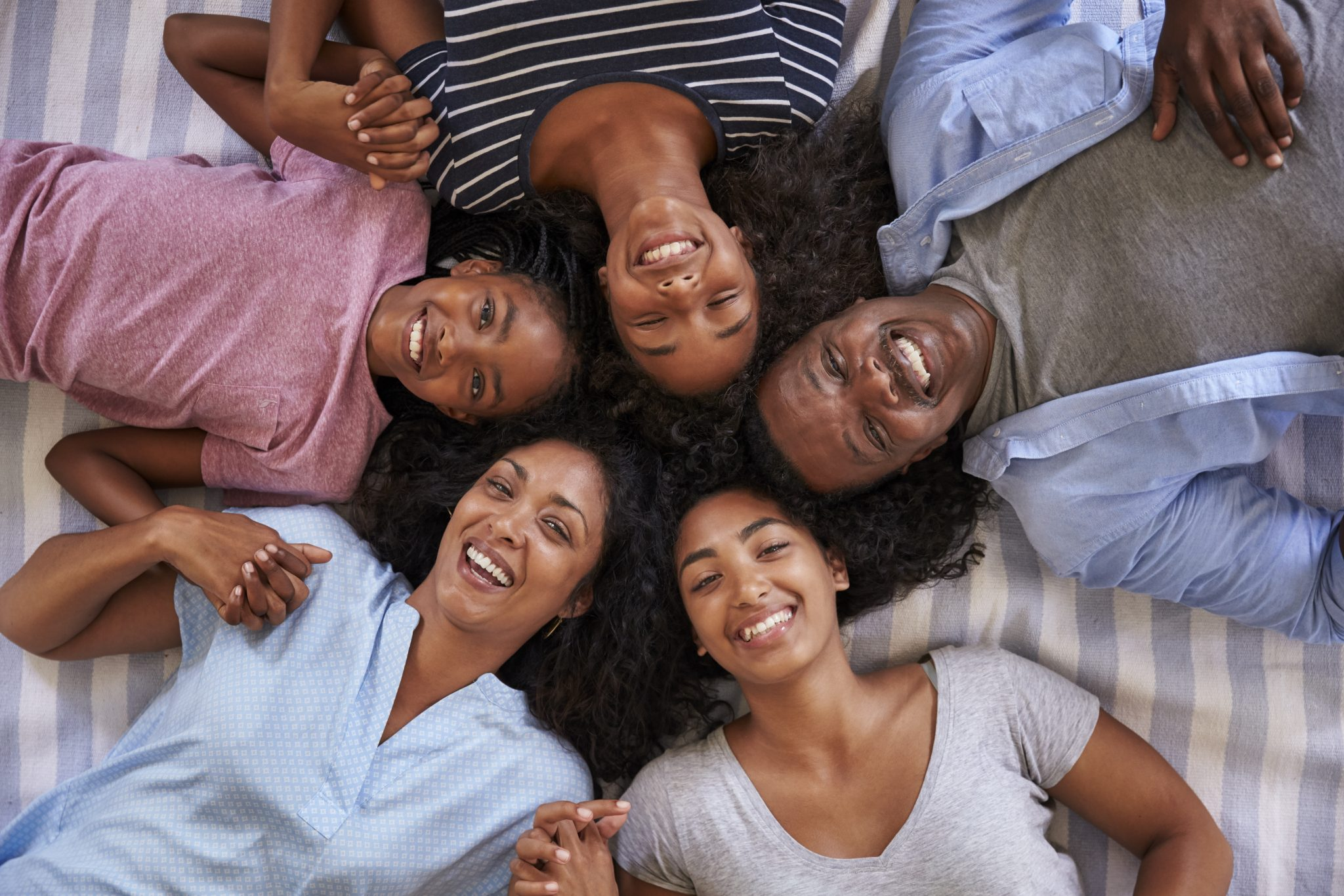 Overhead View Of Family With Teenage Children Lying On Bed