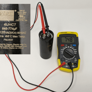 Figure 11. A capacitance meter is shown with the two probes placed on the two capacitor tabs. This capacitor label shows a capacitance of 645 to 774 μF. The meter is reading a capacitance of 748 μF, which is in the acceptable range. The capacitor is good.