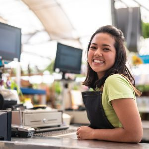 A young woman standing in front of a cash register.