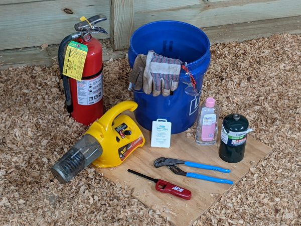 Figure 1. Tools to perform a smoke test: insect fogger, lighter, channel locks, smoke emitters, oil, propane cylinder, safety glasses, leather gloves, fire extinguisher, and bucket of dirt or sand.