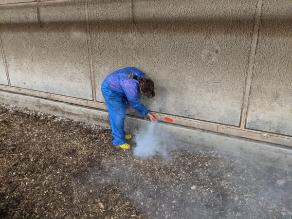 Figure 13. Mark all locations where smoke enters the house perimeter with something bright and easy to see: marking tape, spray paint, etc. Here we are using red tape to identify a large leak at the base of the tunnel door.