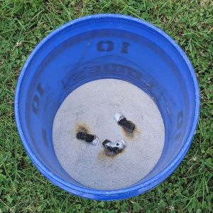 Figure 5. Drop spent smoke emitters into a bucket of sand to prevent a fire hazard.