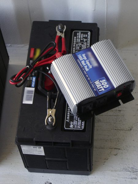 Figure 3. A DC to AC power inverter (blue and silver box) sitting on top of a deep cycle battery. These represent components typical of a small solar stand- alone application, such as an outbuilding or green house.