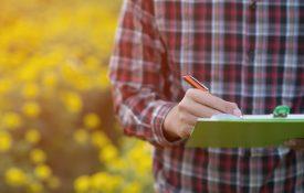 Farmer writing on a clipboard