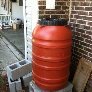 Figure 34. Finished rain barrel, slightly elevated, under gutter downspout